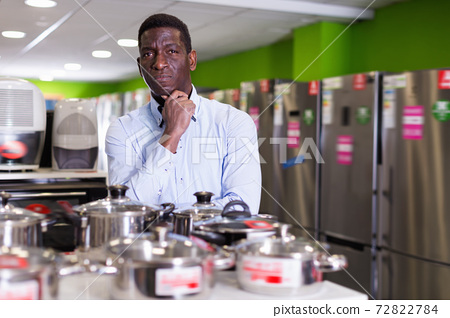Man selecting cooking pot in household appliances section in store 72822784