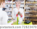 Seller helping customer to choose care products 72823470