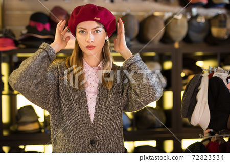 Woman trying on hat during shopping 72823534