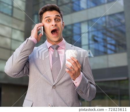 Surprised businessman talking on phone 72823611