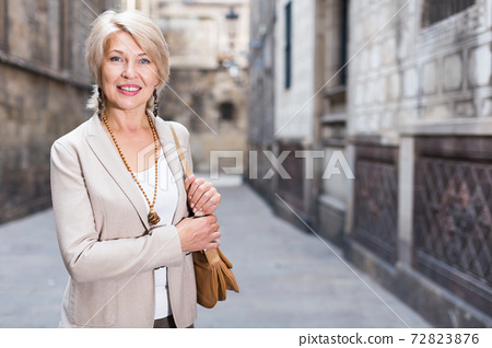 Cheerful mature female is walking in classic jacket 72823876