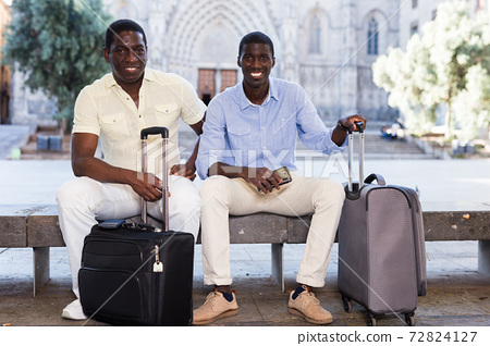 Two african american travelers sitting with luggage on bench 72824127
