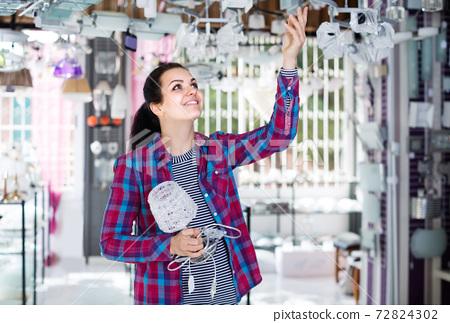 girl in lighter shop choosing modern glass chandelier for house interior 72824302