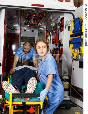 Paramedic team moving man on stretcher 72824918
