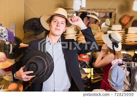 portrait of young guy try on panama at headwear store 72825030