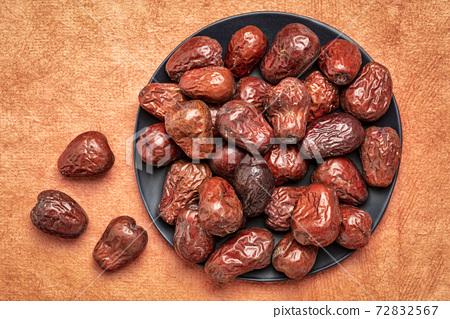 dried jujube fruits on a black plate 72832567