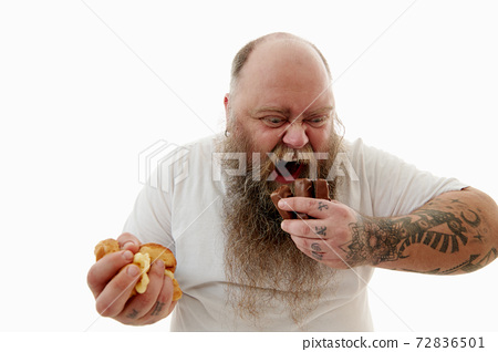 An overweigh caucasian bearded man in white t-shirt consuming unhealthy but delicious junk food. Wildly looking at chocolate bars. Isolated on a white background 72836501
