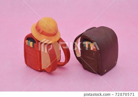 紅色和棕色的學校細胞,用粘土製成的粉紅色的背景,黃色的帽子 72870571