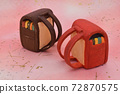Red and brown school bags made of clay on a pink background 72870575