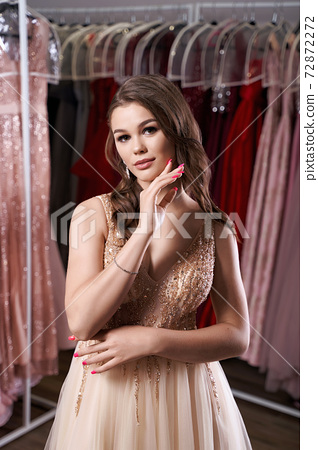 Young beautiful brunette girl wearing a full-length beige yellow champaign chiffon slit prom ball gown decorated with golden sparkles and sequins. Dress hire service with many dresses on background. 72872272