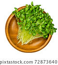 Fenugreek microgreens in a wooden bowl. Ready to eat green sprouts and shoots of Trigonella foenum-graecum. Used as herb, vegetable and in traditional medicine. Close-up, from above, macro food photo. 72873640