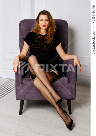Pretty lady sits in armchair in short black dress with tiger pattern 72874646