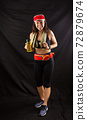 Beautiful girl in jogging red uniform, drinks water after training in the studio on a black background 72879674