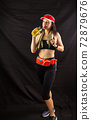 Beautiful girl in jogging red uniform, drinks water after training in the studio on a black background 72879676