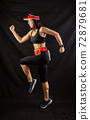 girl in red jogging uniform runs in the studio on a black background 72879681