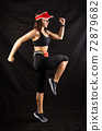 girl in red jogging uniform runs in the studio on a black background 72879682