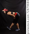 Beautiful girl in a jogging red uniform warming up before training in the studio on a black background 72879684