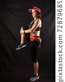 Beautiful girl in a jogging red uniform warming up before training in the studio on a black background 72879685