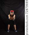 Beautiful girl in a jogging red uniform warming up before training in the studio on a black background 72879689
