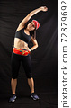 Beautiful girl in a jogging red uniform warming up before training in the studio on a black background 72879692