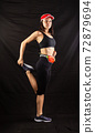 Beautiful girl in a jogging red uniform warming up before training in the studio on a black background 72879694
