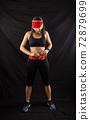 Beautiful redhead girl in jogging uniform posing in studio on black background 72879699