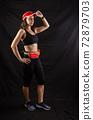 Beautiful redhead girl in jogging uniform posing in studio on black background 72879703
