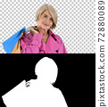 Beautiful senior woman in trench coat holding shopping bags, Alp 72880089