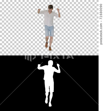 Cheerful young man in casual clothes dancing happily while walki 72880090