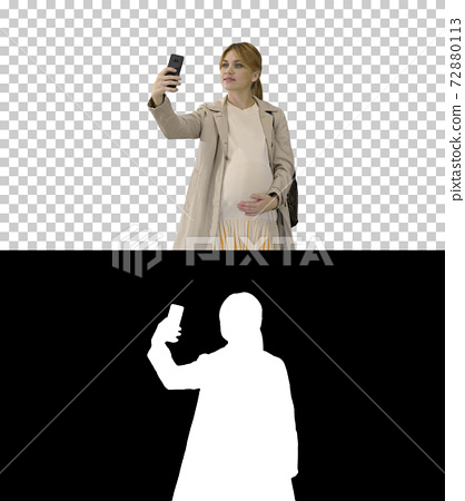 Happy young pregnant woman taking selfie, Alpha Channel with Sil 72880113