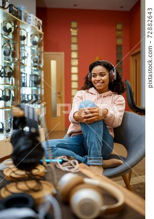 Buyer trying on headphones in audio store 72882643