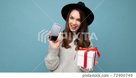 Shot of pretty smiling positive young brunette woman isolated over blue background wall wearing 72900749