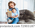 Asian mother reading with her son in the living room at home. People lifestyle and leisure activity. Kids and baby concept 72903187