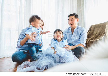 Happy Asian family smile and laugh together in bedroom at home. Two parents and children. People lifestyle in state quarantine after travel on Covid-19 or Coronavirus epidemic concept. Bed foreground 72903192