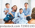 Happy Asian family smile and laugh together in living room at home. Two parents and two children kids. People lifestyle in state quarantine after travel on Covid-19 or Coronavirus epidemic concept 72903193