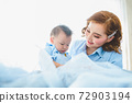 Asian mother and her son wearing blue shirts on bed in bedroom with copy space at home. People lifestyle and Newborn medical concept. State quarantine in Covid-19 or Coranavirus epidemic theme 72903194