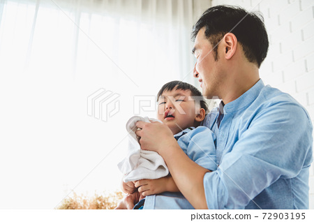 Asian Japanese father consoling his crying son and wiping tears in bedroom at his home white curtain background. People lifestyle health. Medical and Health concept. Negative emotion theme. 72903195