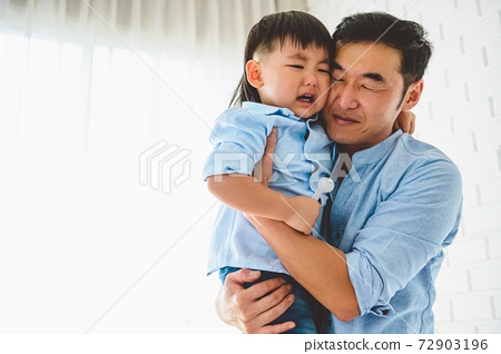 Asian Japanese father carrying and consoling his crying son in bedroom at his home with window and white curtain background. People lifestyle health. Quarantine in Covid-19 or Coranavirus epidemic 72903196
