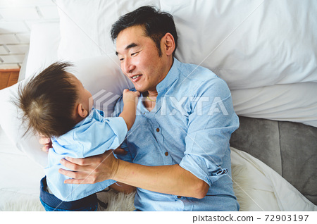 Asian father and son playing together on white bed in bedroom in the morning. Two people having leisure time at home. People lifestyle concept. 72903197