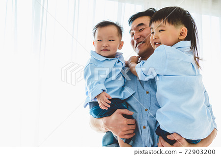 Happy father carrying two children in bedroom at their house. Family living and having positive expression emotion togetherness. Leisure time. People lifestyle health. Quarantine Covid-19 Coranavirus 72903200