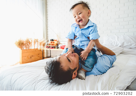 Two Asian father and his son are lying and playing in bed at bedroom. Child on top of Japanese dad body happily. Leisure time. People lifestyle health affection love. Quarantine Covid-19 Coranavirus 72903202