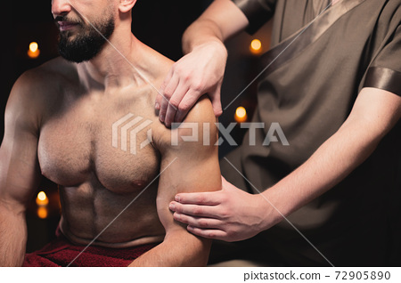 Male athlete has a massage of the shoulder and upper arm muscles in the dark room of the spa massage parlor 72905890