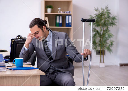 Young leg injured male employee working in the office 72907282