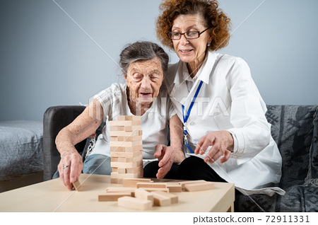 Senior woman practice skills, build wooden blocks, build tower and try not to let it fall, Jenga game. Old patient pull out block, place on top, support doctor during therapy dementia in house 72911331