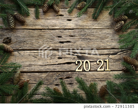 2021 New Year.Christmas greeting background for postcards, web pages and greetings.Fir branches on a wooden ancient background with place for text. 72911385