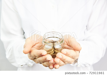 Hand with coins in a glass jar. Money growth and savings concept 72911981