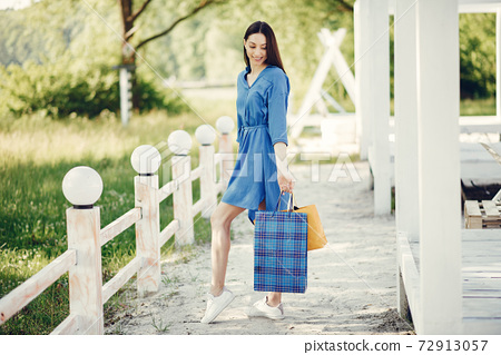 Cute girl with shopping bag in a park 72913057