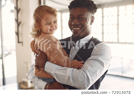 Black man with white daughter standing in a cafe 72913078