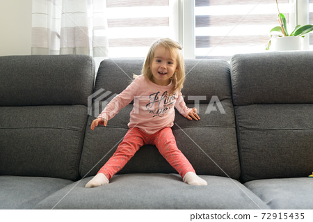 2 year old baby girl on couch in bright interior. 72915435