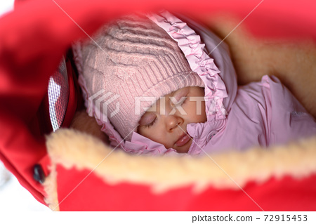 Cute baby in stroller on frosty winter day. Baby wearing woolen warm hat and mittens 72915453